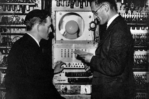 The control panel of the automatic sequence-controlled calculating machine at Manchester University; showing the monitor cathode-ray tube with Dr. T. Kilburn (left) and Professor F. C. Williams (right), inventor of the memory storage system
