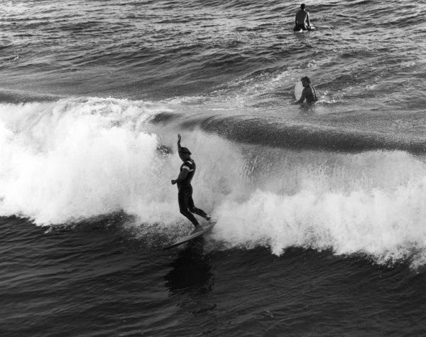 Surfing at Pismo Beach, south California, U.S.A. Date: late 1960s