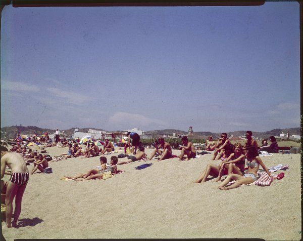 Young people, holidaymakers, sunbathing on the beach at Callela de la Costa, Costa Brava, Spain