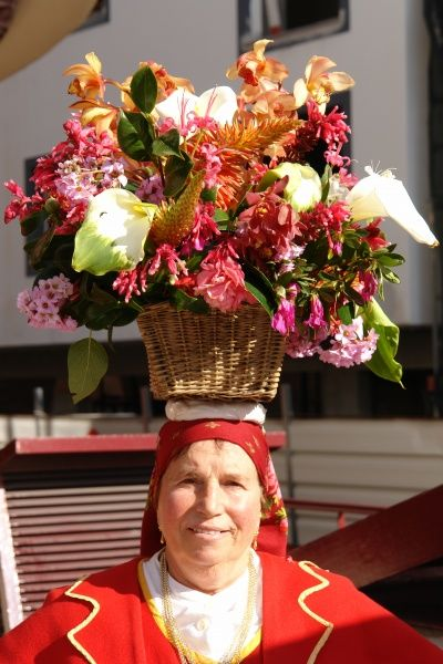 A woman from a folklore group from the village of Camacha, walking through the streets of Funchal, the capital city of Madeira, with a large basket of flowers on her head