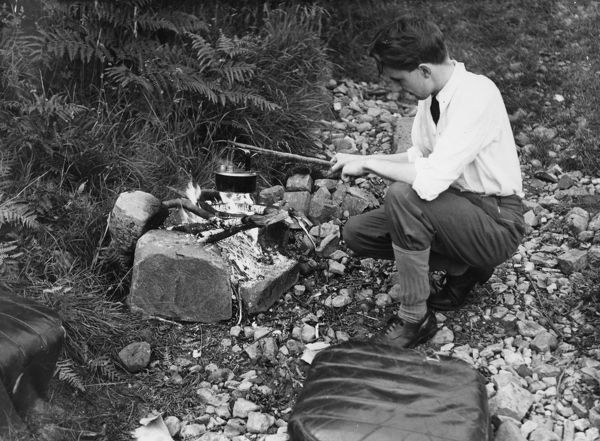 A smart young man boiling a kettle over a camp fire. Note the car seats close by for extra comfort!