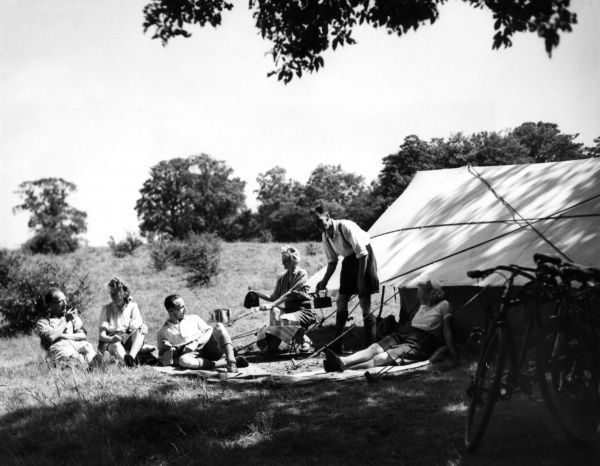 Three happy couples enjoy a meal on a campsite at Tyler's Causeway, Hertfordshire, England. Date: 1930s