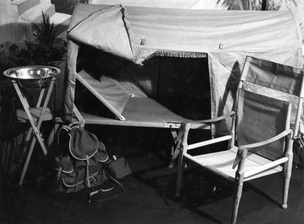Camping equipment, comprising of a bed and tent in one, with head support, a comfortable canvas chair, a wash bowl on a stand and a rucksack and water flask - luxury! Date: 1935
