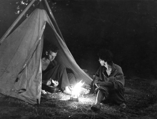 Young men preparing supper from their tent, pitched on the banks of the River Danube, Hungary. Date: 1930s