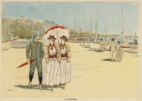 Two ladies under a parasol and a gentleman take a stoll between the boats on the Cannes seafront