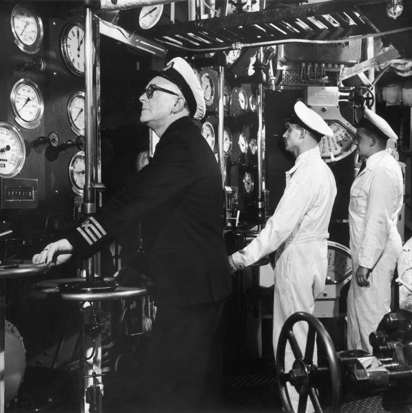 A ship's captain and two of his crew check a number of dials. Photograph by Heinz Zinram