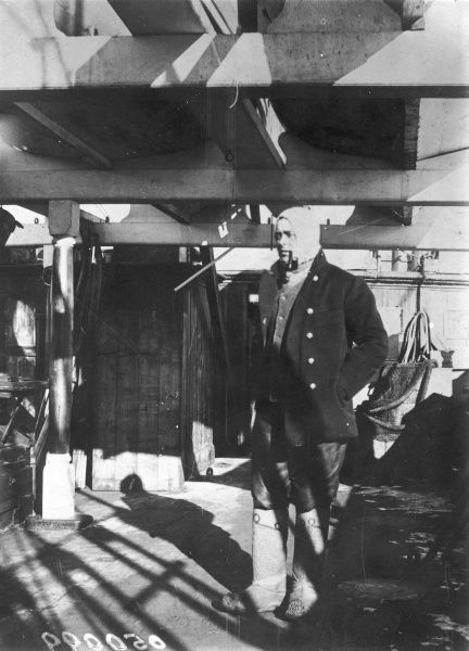 Captain Robert Falcon Scott (1868 - 1912), British Polar explorer, pictured on board the Terra Nova wrapped up against the cold and smoking a pipe, prior to the ill-fated expedition to the South Pole in which he and his four team mates perished