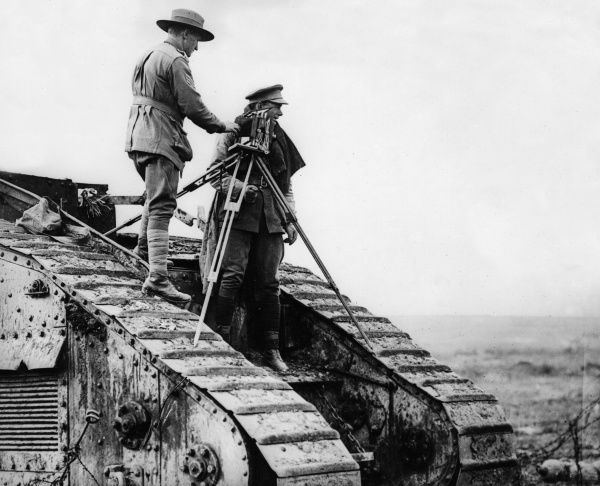 Captain George Hubert Wilkins (1888-1958), Australian official war photographer, setting up his camera and tripod on top of a tank near Roussoy, northern France, towards the end of the First World War. He was also, at various times, a polar explorer