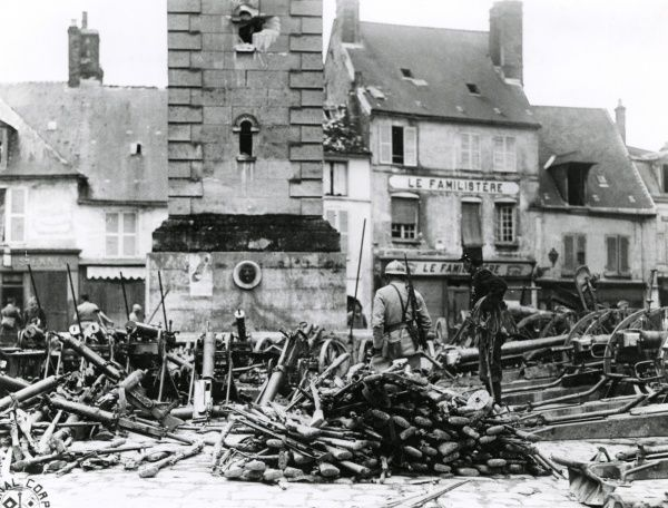 Allied soldiers looking at piles of captured German weapons in the main square of Villers-Cotterets, northern France, towards the end of the First World War. Date: 27 July 1918