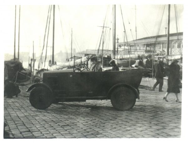 A car sits at the docks with a well-dressed woman in the front and a man in a flat cap in the back. In the background is a forest of ships' masts and rigging