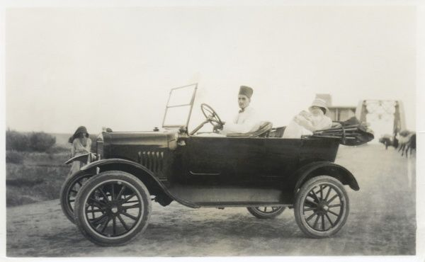 An open-topped car with an Eastern driver and a European mother and baby in the back, somewhere in the Middle East