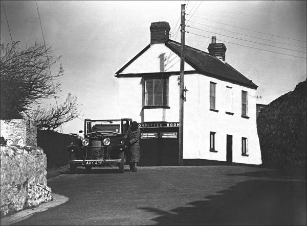 A Vauxhall Cadet car and its driver in front of a large white house in Irsha Street, Appledore, Devon