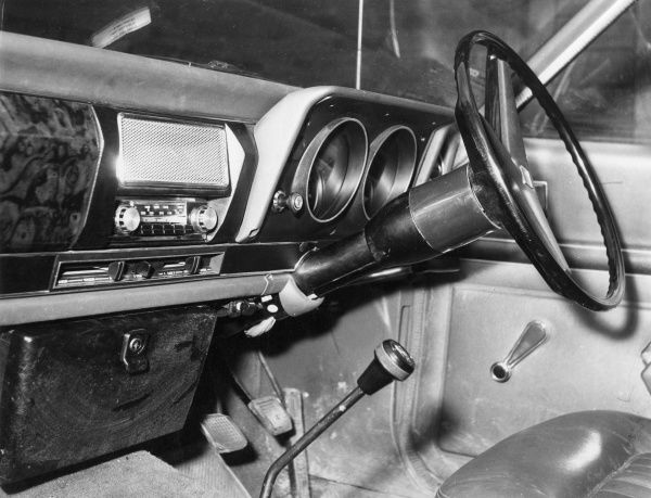 The interior of a car, sjowing the dashboard, glove compartment, radio, choke, gear stick, steering wheel, etc. Date: 1970s