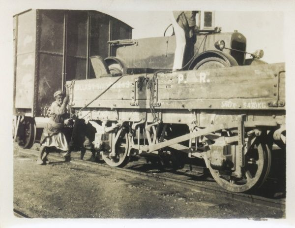 A car being loaded onto a train, somewhere in the Middle East