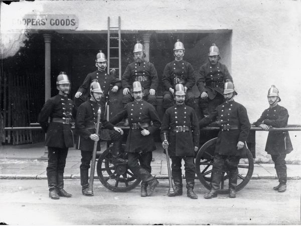 Ten members of the Carmarthen fire crew pose for their photograph outside Coopers' Goods in Carmarthen, the county town of Carmarthenshire, Dyfed, South Wales. They are in full uniform, with their fire engine and a ladder