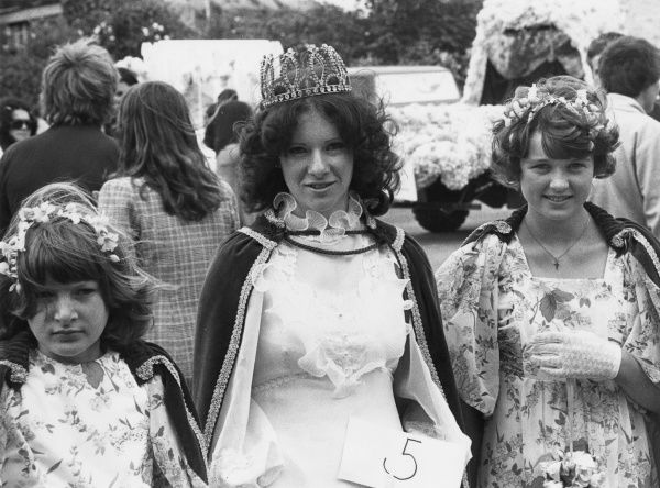 A carnival queen wearing a crown and cape, and her two attendants in floral dresses