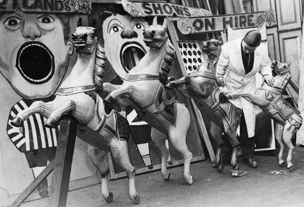Retouching the paintwork on traditional wooden carousel horses before the start of the travelling fair season, Britain. Date: 1930s
