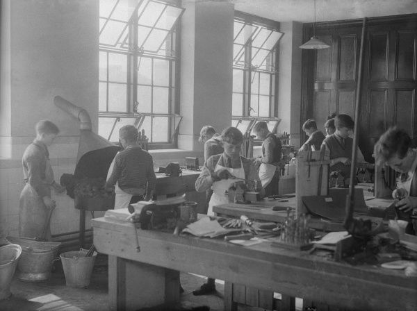 A class of boys learning carpentry. Date: early 1930s