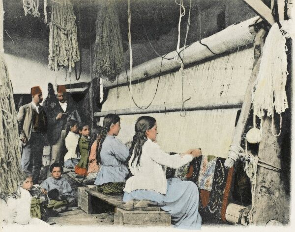 Kula, Turkey. Women and children make carpets on a large loom, while two men in fez hats oversee proceedings. Renowned for volcanic rock formations as well as carpets