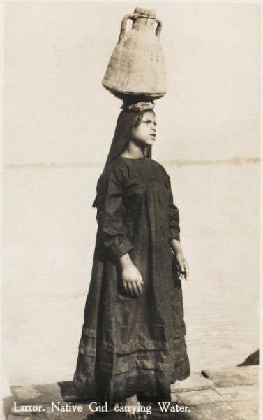 Luxor, Egypt - Native girl carrying water on her head in a large amphora