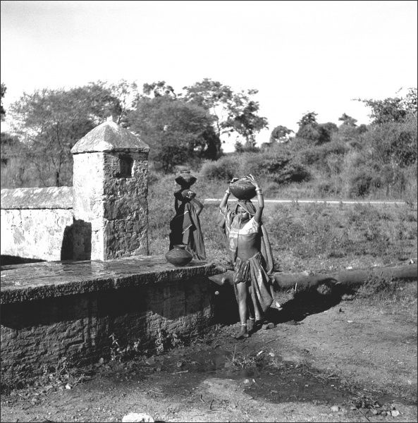 Two Indian women carry water from a well on their heads in large pots - Mandu, Madhya Pradesh Province, India. Photograph by Ralph Ponsonby Watts