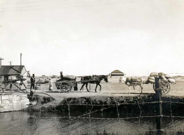A horse and cart and a mule and cart approaching each other on a bridge, somewhere in the Middle East