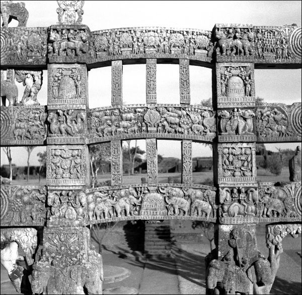 An ornately carved gateway to the Stupa at Sanchi, Madhya Pradesh Province, Central India. The Stupa is a large hemispherical dome with a central chamber containing relics of the Buddha. Photograph by Ralph Ponsonby Watts