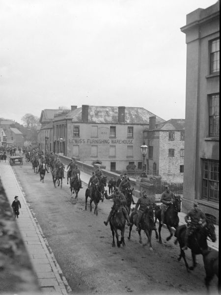 A cavalry parade crosses New Bridge into Victoria Place in Haverfordwest, Pembrokeshire, Dyfed, South Wales, probably around the time of the outbreak of the First World War. Lewis's Furnishing Warehouse can be seen in the background