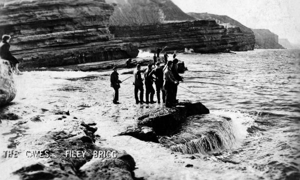 View of the Caves at Filey Brigg, North Yorkshire, with people fishing. Date: 1940s