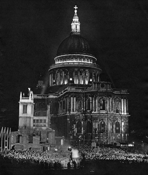 A celebration outside St Paul's Cathedral, City of London, on the evening of 3 May 1951, the opening day of the Festival of Britain. About 5000 young people gather on a cleared bomb site behind the Cathedral to sing around a large bonfire