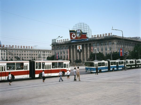 The Central History Museum in Kim Il Sung Square, Pyongyang, capital of North Korea, with a line of buses or trams in the foreground