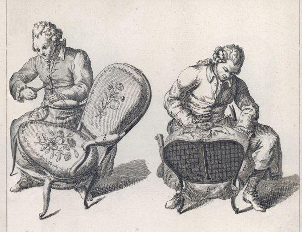Two French craftsmen work on the elaborate upholstery on a pair of Louis XV style Fauteuils (armchairs)