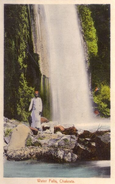 Chakrata, Northern India - The Waterfalls. The Indian gentleman standing in close proximity to the falls is rather sensibly holding a black umbrella! Date: circa 1910s