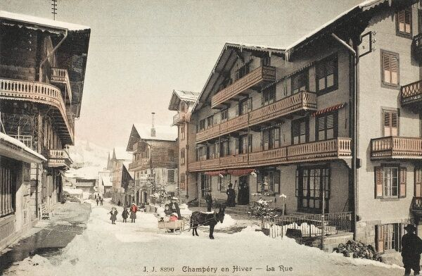 Street in Champery, Switzerland. A small child takes a ride in a mule-pulled sleigh. Famous ski resort and tourist destination