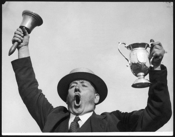 Mr. Gomer Thomas, winner of the National Town Criers' Championships of England and Wales, at Marlborough, Wiltshire, waving his Champtionship Cup aloft!