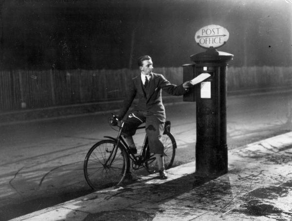 A smart cyclist wearing 'Plus Fours' stops to pop a letter into a Royal Mail pillar post box. Date: 1930s