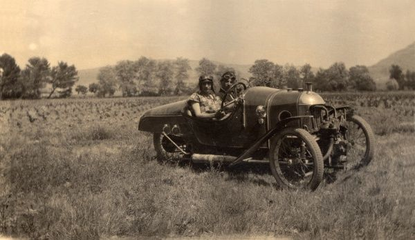 Two chaps in full driving attire park their sporty three-wheeler in a field
