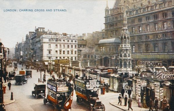 Looking east along the Strand, with Charing Cross station on the right ; motor buses and taxi-cabs drive past Queen Eleanor's Cross