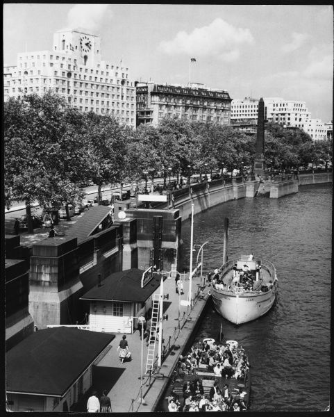 A busy scene at Charing Cross Pier, Victoria Embankment, London, showing tourists enbarking on or alighting from boat trips up and down the River Thames, London