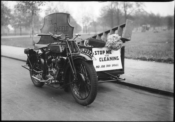 The motorcycle of the 'Royal Enfield' travelling charlady with its hopeful sign: 'Stop me for cleaning, no job too small' and mop and bucket ready 'to go'!
