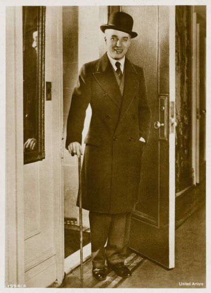 CHARLIE CHAPLIN (Sir Charles Spencer) English comedian and actor walking through a doorway