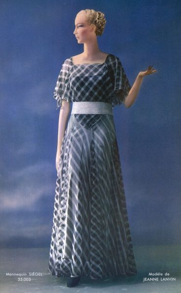 A gown by Jeanne Lanvin using a diaphanous striped fabric overlaid to produce a diagonal check effect. It has a square neckline & a gored skirt & is worn with a broad silver belt