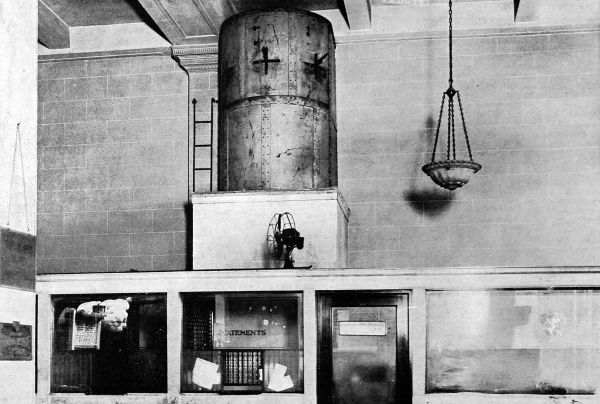 Photograph of the precautions taken against bank robbers in America during the 1920's. A steel armoured tower hides two armed guards to defend the building