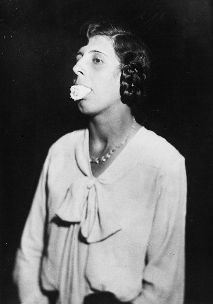 Ethel Beenham, Harry Price's secretary, demonstrates how a sheet of cheesecloth 2 metres by half a metre can be fitted into a deceiving medium's mouth or other orifice