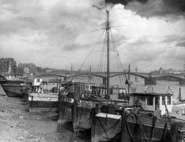 Stretching along the foreshore to the west of Chelsea Bridge, London, is this long line of old sailing barges. This 'Barges Graveyard' houses many bohemian artistic Londoners. Date: 1940s
