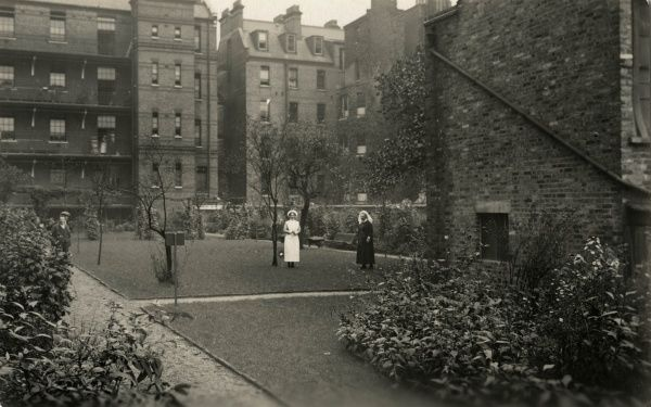 The grounds of what is believed to be the workhouse infirmary at Cale Street, Chelsea, London. A uniformed matron and nurse stand at the centre while two men look on. The infirmary later became St Luke's Hospital