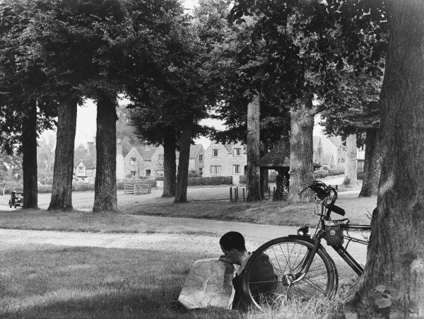 A man reads a map while his bicycle leans against one of the beech trees in the quiet village of Chenies, Buckinghamshire