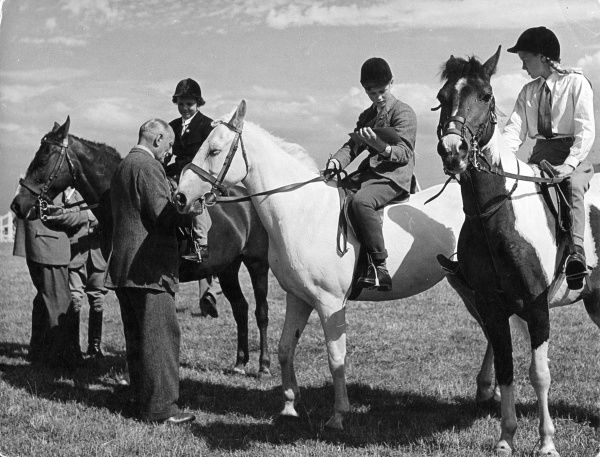 'Junior' competitors receive their award cards from one of the judges at a horse show at Heswall, Cheshire, England. Date: 1950s