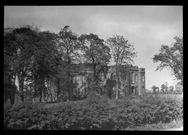 View through trees of Cheshunt Great House, at Cheshunt, Hertfordshire. The building dates back to the 15th century. For much of the the 19th and early 20th centuries it was used as a Freemasons hall. It was demolished in 1970 following a fire