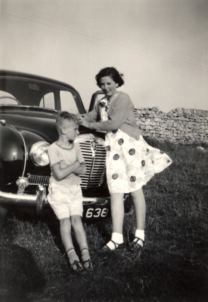 A girl and her younger brother leaning against the front of A fine Austin A40 on a windy day